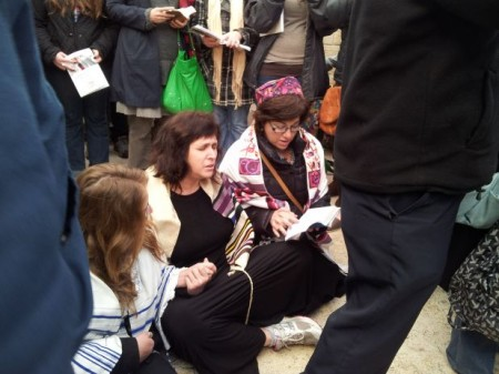 Three women at the Kotel today with Women of the Wall wear tallitot and sit on the ground, arm in arm; courtesy WoW.