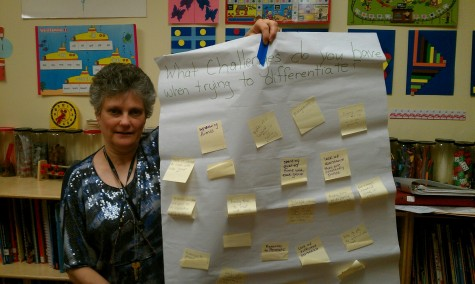 """Curriculum Coordinator Karen Simon holds up a sheet on which teachers placed post-it notes answering the question, """"What challenges do you have when trying to differentiate?"""" Photo courtesy."""