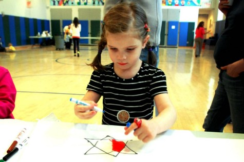 A young girl puts thought into her matzoh cover design. Photo from SmallCity@Senesh; courtesy The Covenant Foundation
