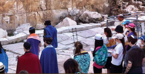 Community day school students pray at a discrete distance from the Kotel plaza