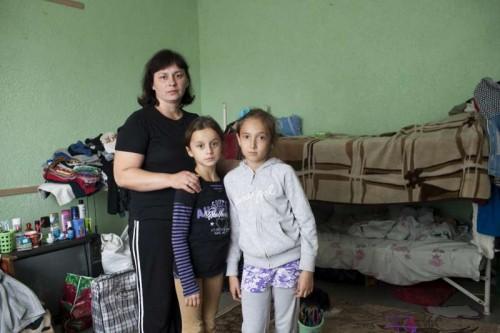 A Ukrainian mother poses with her daughter and a young friend in the room where she lives with her family in a centre for displaced people in Slavyansk. Most of the people are from the Luhansk and Donetsk regions.