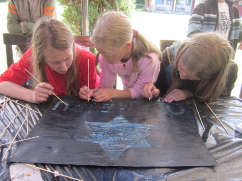 Girls from Lithuania work on a scratch magic Olameinu sign.