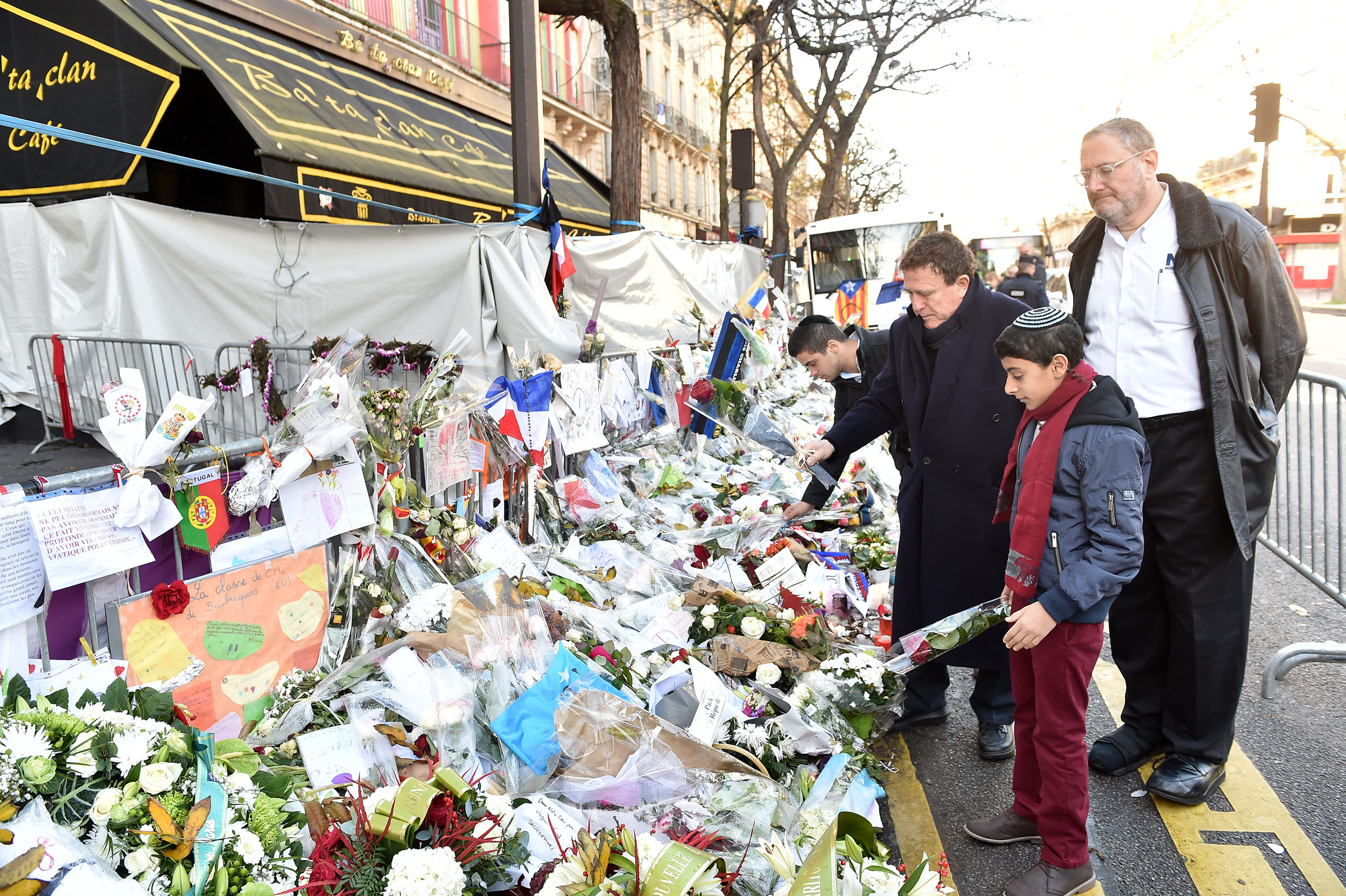 Nachum Segal looks on as Yehoram Gaon and Ouzia Tzadok lay flowers outside the Bataclan theater in Paris, site of one of six coordinated Islamist terror attacks last month. Photo by Israel Bardugo.