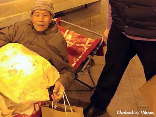 Accepting a bag of food in time for the Chinese New Year. Photo courtesy Chabad.org/News.